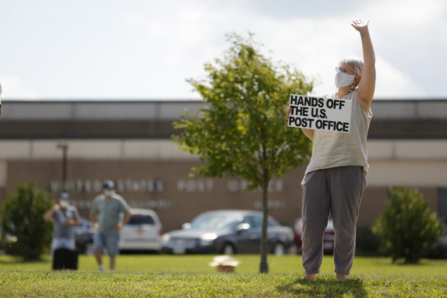 Rose Weisburd, 55, of Carbondale, IL, waves at passing motorists that honked their car horn in support of Weisburd and a group of about 19 other protesters outside the main post office in Carbondale.  The group of protestors gathered in solidarity with a nationwide call for a #SaveThePostOfficeSaturday rally on Saturday, August 22 ,2020. MoveOn, the NAACP, WorkingFamiliesParty, Indivisible and other national organizations announced the nationwide effort to show up at post offices across the country at 11Am on Saturday, August 22,