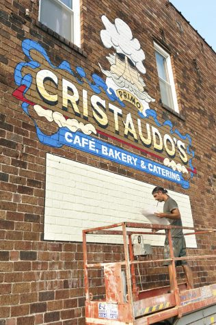Jared Davey, 40, from Carbondale, IL, is in charge of painting all of the logos of the businesses which occupy the building. Davey worked on the Cristaudo