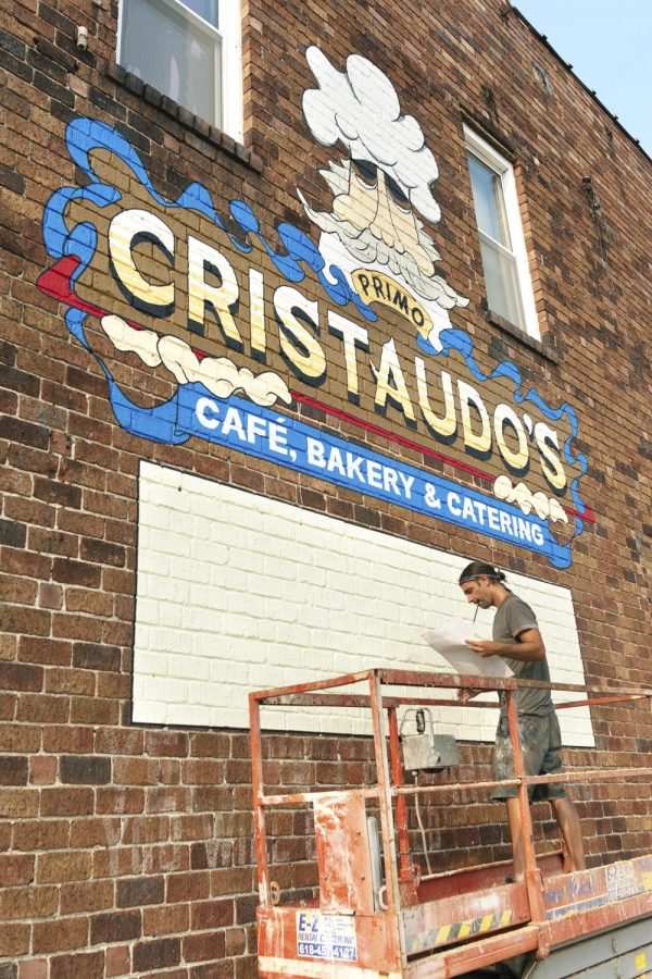 "Jared Davey, 40, from Carbondale, IL, is in charge of painting all of the logos of the businesses which occupy the building. Davey worked on the Cristaudo's logo on Wednesday, Sept. 9, 2020, in Carbondale, ILL. ""It is my interpretation of the logo,"" Davey said when talking about the Cristaudo's logo which was originally created by Bob Hunter. Davey became a full-time artist in 2013, originally doing screen printing and sign painting for a few years. Another main sign painting job that Davey had was a mural at PK's Bar. See more of Davey's art at @jaydayvee."