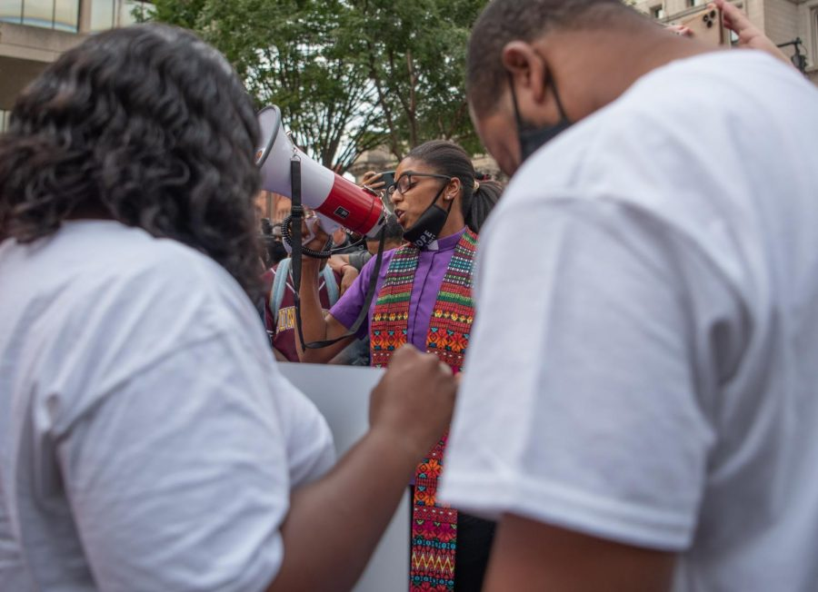 Rev. Stachelle Bussey prays with members of Breonna Taylor's family before the march begins Friday, September 25, 2020 in Louisville Kentucky.