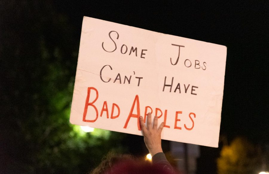 """A protester holds sign towards passing drivers emphasizing """"some jobs can't have bad apples on September 25, 2020 in Carbondale, ILL."""