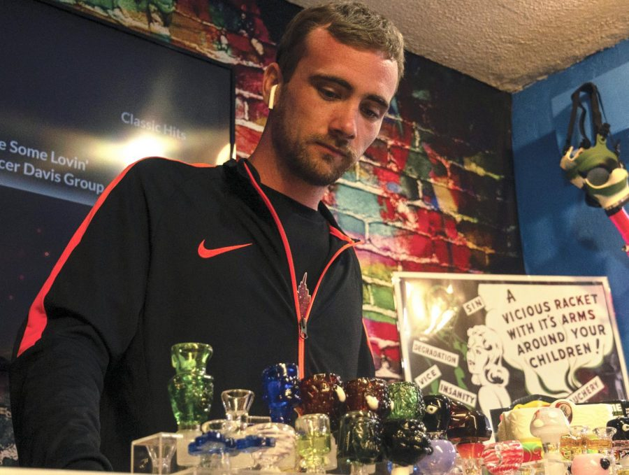 "Cody Stanton of Hemp-N-Stuff displays several glassware pieces for customers on Tuesday, Sept. 22, 2020 in Carbondale, ILL. Hemp-N-Stuff is a brand new smoke shop in Carbondale IL. It is family owned and operated by the Stantons. They do monthly giveaways for their customers and have a variety of products including glassware, pipes, cleaning materials, and more. You can find them at 828 East Main Street, Suite A, every week Monday - Friday 9am - 8pm, on Saturdays from 10am - 8pm, and Sundays from 12pm - 8pm. ""We've been open for a bit and we have a decent customer base. Some days it's busier than others but I think COVID has a lot of impact on that,"" said Stanton."