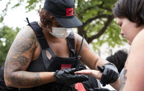 Kara Rexx, a volunteer medic, checks the finger of protester at Jefferson Square Park in Louisville, Ky. on Sept. 25.