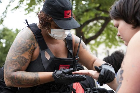"Kara Rexx, a volunteer medic, checks the finger of protester at Jefferson Square Park in Louisville, Ky. on Sept. 25. ""The kinds of injuries depends. There"