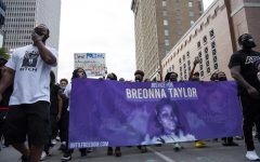 Protesters of the grand jury's decision in the death of Breonna Taylor carry a sign in her memory during a march through Louisville, Ky. on Sept. 25.