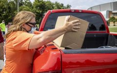 One of the members of the Laborers' Local 773, Mary Smith, loads a box of produce into a truck at Pandemic Relief Food Distribution event in front of the Banterra Center. Smith says,
