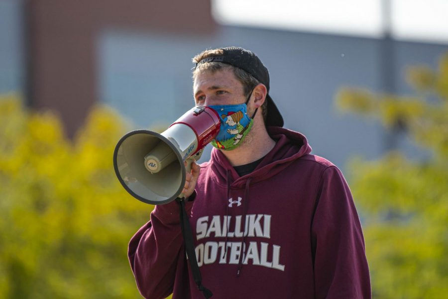 Jack Wearden, SIU football student assistant, congratulates people on a megaphone as they finish the Run/Walk event.