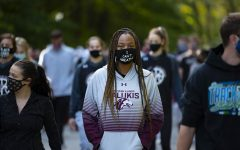 Kyra Hunter, SIU volleyball player, walks among other student-athletes at SIU during the Run/Walk event put on by the Saluki Unity. Hunter wears a face mask with
