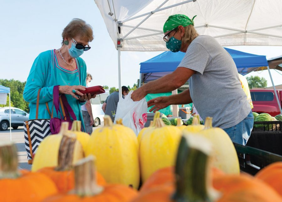 "Virginia Rinella buys watermelons from Richard Bochantin at the Humpday Farmer's Market on Wednesday, Sept. 30, 2020, in Carbondale, ILL. ""This is my first experience [here] and I like it"" Rinella said. Bochantin has been selling his products at the farmer's market for about 4 years. Bochantin said that after COVID-19 started, the city shut down the farmer's markets on city property, so they decided to move to a new location, the parking lot of Gold's Gym in Carbondale, ILL. Bochantin said that since moving to the new location they have seen more people stop by."