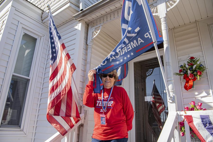 Doris Miller, 87, smiles as she removes a part of the Trump flag that got blown into her face Saturday, Oct. 17, 2020, in Vienna, Ill. Miller, an avid Trump supporter, sells Trump merchandise in her front yard to help raise money for President Trump.