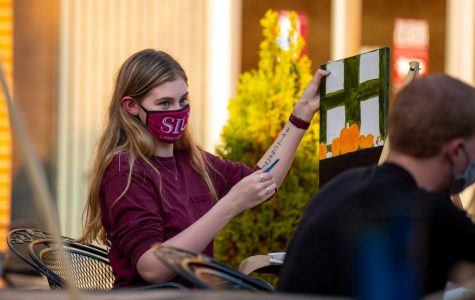 SIU student, Jordan Smearman, shows off the progress on her painting during the Painting on the Patio event at the outside of the Student Center Wednesday, Oct. 21, 2020. The event held a limited amount of people where painters could gather together to paint a fall themed subject.