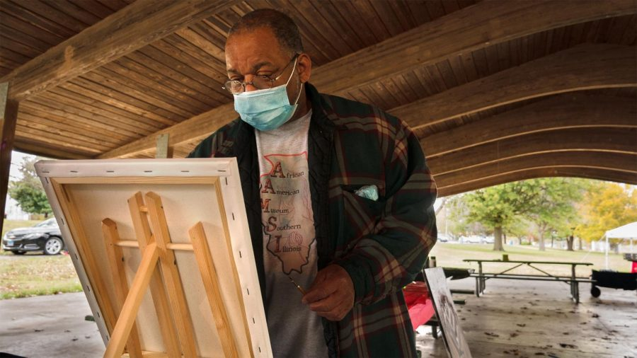 """SIU professor of fine arts, Najarr Abdul-Musawwir follows along with a paint demonstration held by Cree Glanz of Project Human X at the Southern Illinois Unity Coalition's Stop the Violence event Saturday, October 24, 2020, at the Attucks Park Pavillion in Carbondale, Ill. Abdul-Musawwir is the president of the African American Museum of Southern Illinois. """"We're sponsoring this right here for the Stop the Violence program. We also have artifacts that we brought out so that people can be able to appreciate African aestheticism within the African community as well as non-African American communities,"""" Abdul-Musawwir said."""