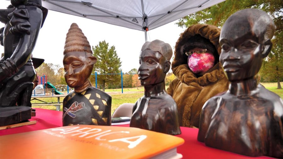 """Treasurer of the African American Museum of Southern Illinois DeSande R attends a pop up exhibit of African artifacts at the Southern Illinois Unity Coalition's Stop the Violence event at Attucks Park Saturday, October 24, 2020, in Carbondale, Ill. """"We're having safe activities to show that we can do something safe in Carbondale, and everybody is invited….It's scary. I hear gunshots all the time where I live and I'm not even in a bad neighborhood….I just hope they can stop this soon, its running rampant,"""" DeSande said."""