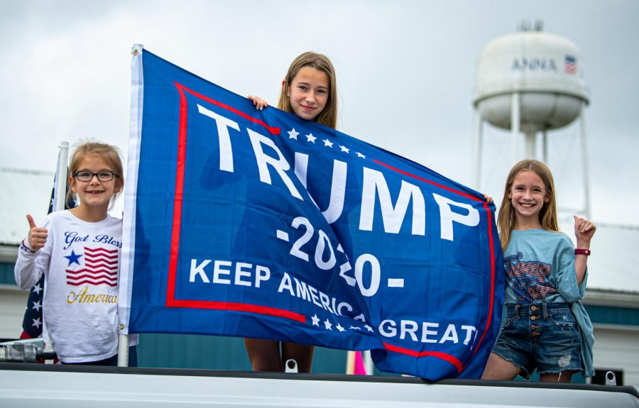 Hailie Sullivan, left, 8, Lauren Ecker, 13, Kaitlyn Sullivan, 10, pose for a photo with a Trump flag during the Trump Train event in Anna, Ill. on Saturday, Oct. 10, 2020.