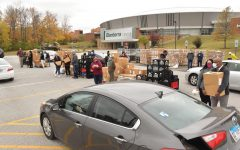 People wait in line at the Pandemic Food Distribution event Monday, Oct. 26, 2020, at the SIU Banterra Center, in Carbondale, Ill. Volunteers help load boxes of food into the cars in line. The food comes from the USDA Farm Table program to help those affected by the pandemic.