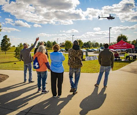 A small crowd watches as a helicopter lands to deliver Splash Duck, the mascot of the event to the Ducky Derby Dash on Sunday, Oct. 4, 2020 at the Walker