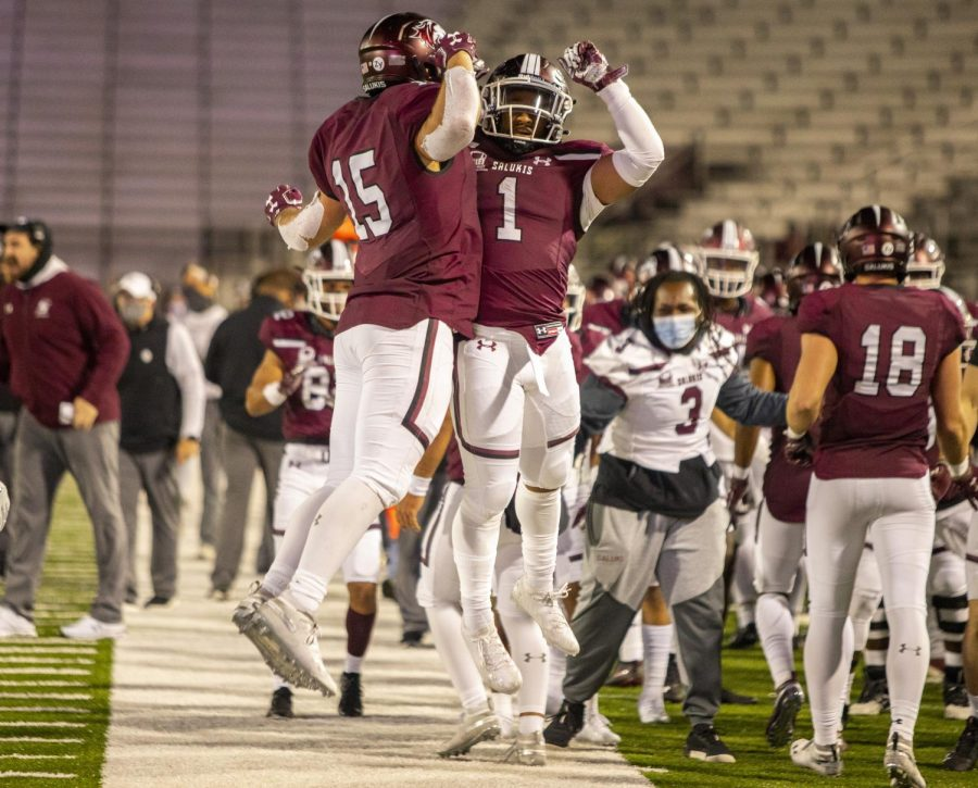 SIU running back Javon Williams Jr., left, leaps into the air to bump fellow teammate Romeir Elliott after Williams 40-yard touchdown run in the Salukis' 20-17 win over the Redhawks on Friday, Oct. 30, 2020 at Saluki stadium in Carbondale, Ill.