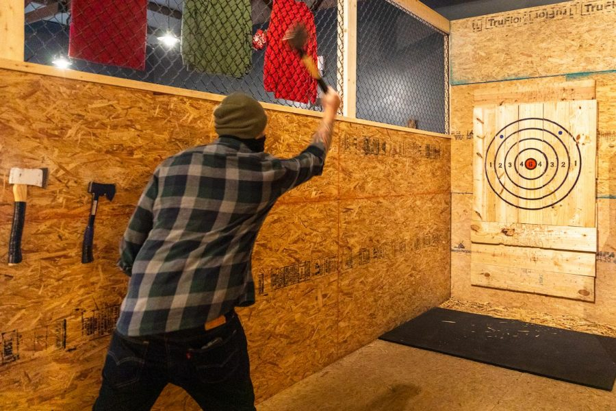 Isaac Gibson, co-owner of Backwoods Axe Throwing in Murphysboro, draws back to throw an axe Thursday, Oct. 29, 2020.