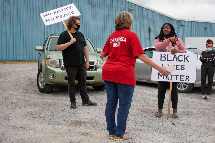 Takiyah Coleman, center, and a group of Black Lives Matter protestors argue with a Trump supporter who refused to give their name at the Trump Train on Saturday, Oct. 10, 2020, in Anna, Ill.