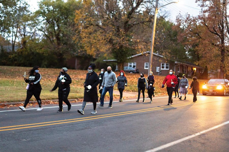 Community members walk quietly in remembrance of Xe'Quan Campbell, a 16-year-old Carbondale Community High School student who was murdered in Nov. of 2019, and to bring awareness to gun violence Friday, Oct. 23, 2020, in Carbondale, Ill. The gathering was organized by the Southern Illinois Unity Coalition and started near the apartment that Campbell was shot at on Freeman St. in Carbondale, Ill. There will also be events going on throughout the weekend of Oct. 24 and 25 to help raise awareness on gun violence.