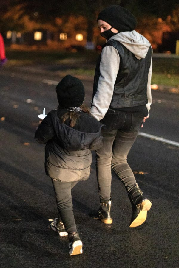 Julian Wells and her daughter, Rumi, 6, march in remembrance of Xe'Quan Campbell, a 16-year-old Carbondale Community High School student who was murdered in 2019, Friday, Oct. 23, 2020, in Carbondale, Ill.