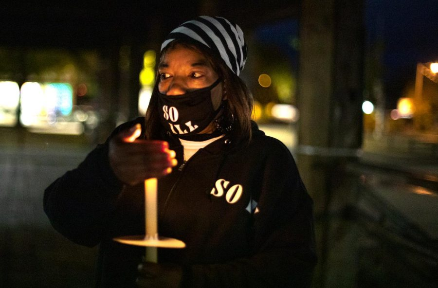 Nancy Maxwell attempts to keep her candle from blowing out due to wind during the moment of silence in remembrance of Xe'Quan Campbell, a 16-year-old Carbondale Community High School student who was murdered in 2019, Friday, Oct. 23, 2020, in Carbondale, Ill.
