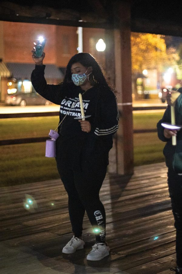Emerald Avril holds a phone flashlight at the Kick Off Candlelight March during a moment of silence in remembrance of Xe'Quan Campbell, a 16-year-old Carbondale Community High School student who was murdered in 2019, Friday, Oct. 23, 2020, in Carbondale, Ill. Those in attendance had to resort to using flashlights instead of candles due to wind.