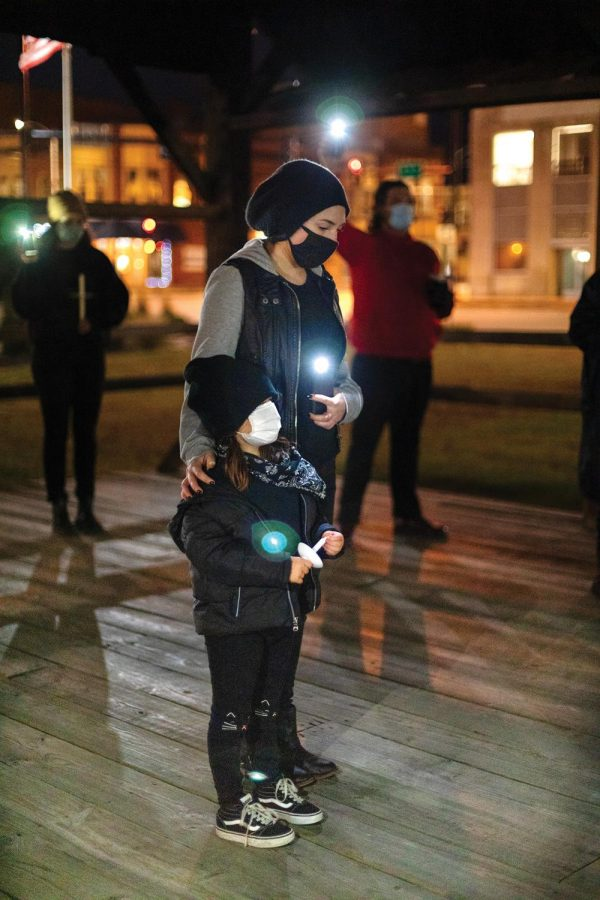 Julian Wells and her daughter, Rumi, 6, observe a moment of silence in remembrance of Xe'Quan Campbell, a 16-year-old Carbondale Community High School student who was murdered outside of a relative's apartment in 2019, Friday, Oct. 23, 2020, in Carbondale, Ill. The memorial march started almost a minute away from where Campbell was shot. The quiet, march was the kickoff event for a weekend of Stop the Violence events hosted by the Southern Illinois Unity Coalition.