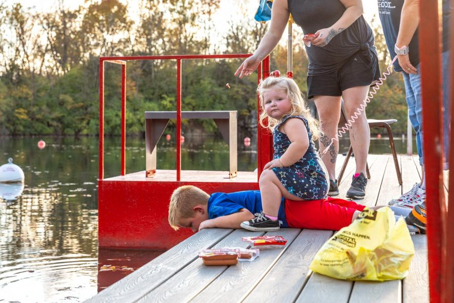 Katie Robison sits on her brother, Landen Robison, while he feeds the catfish at Mermet Springs Thursday, Oct. 22, 2020.