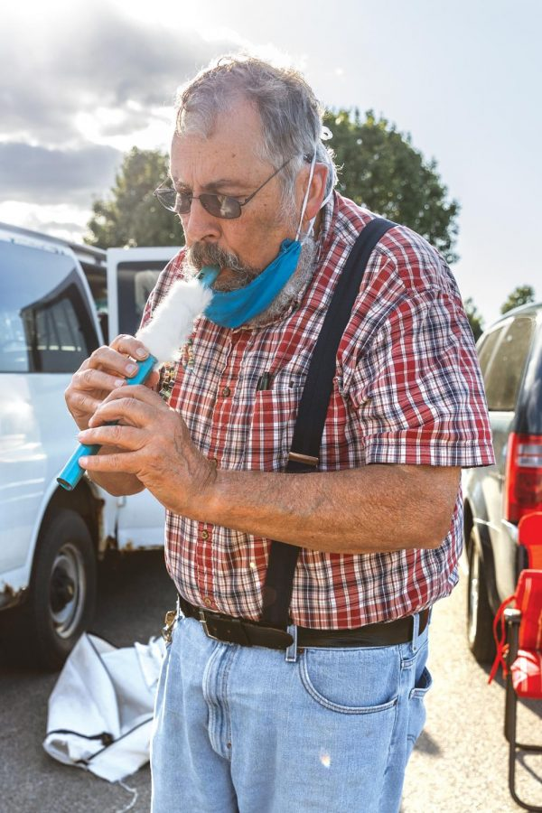 Al Morgan, a local Native American artist, plays a flute at the Humpday Farmer's Market on Wednesday, Sept. 30, 2020, in Carbondale, ILL. Morgan makes and sells jewelry, dreamcatcher, baskets, and more. He began creating art when his wife got sick from Parkinson's as a hobby and has continued to expand the types of art that he makes.