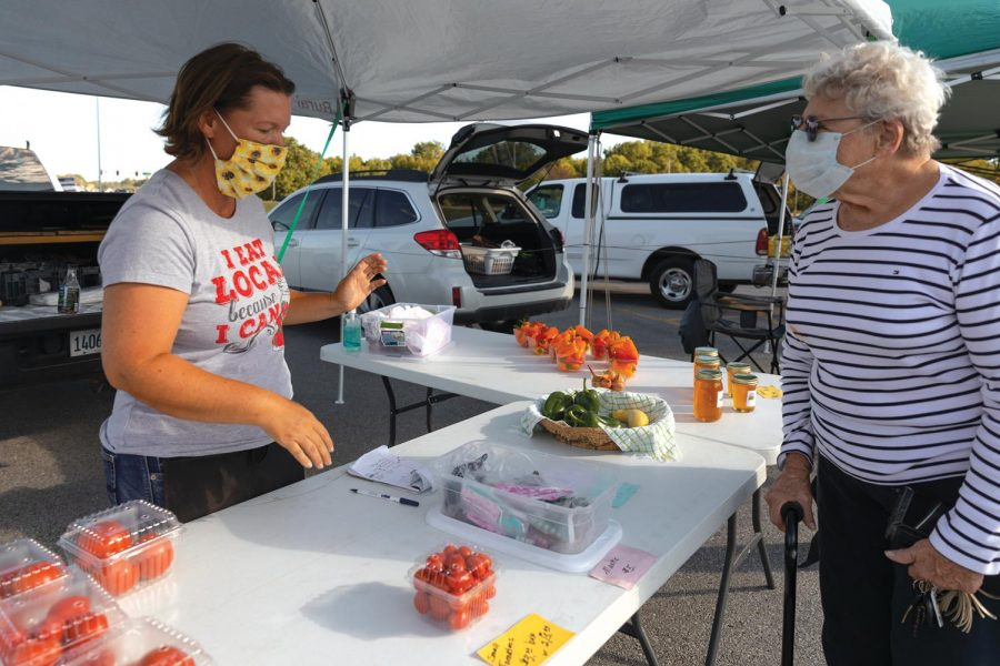 Tonya Green talks with Loraine Reinhardt about the masks made by a farm that she partners with at the Humpday Farmer's Market in Carbondale, ILL., on Wednesday, Sept. 30, 2020. Green sells sweet peppers, green peppers, and squash and the farm that she partners with was selling tomatoes, honey, and masks. Green attends the Humpday Farmer's Market every Wednesday.