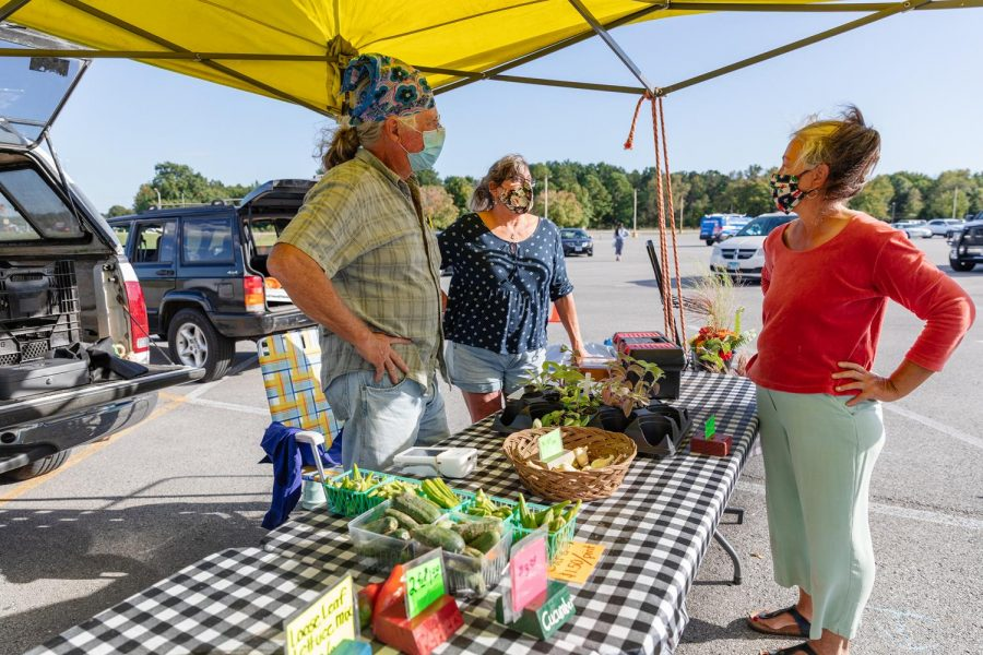 Pam and Ed Hickam, Shade Tree Farm, talk with fellow farmer, at the Humpday Farmer's market on Wednesday, Oct. 30, 2020, in Carbondale, Ill.  Shade Tree Farm sells tomatoes, eggs, cucumbers, okra, garlic, house plants, and Pam does flower arrangements.