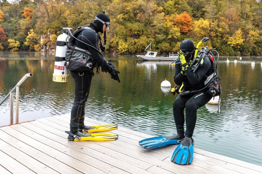 """John Weyers and his son, John demonstrate how to properly dismount a boat while scuba diving by doing a """"back roll"""" Monday, Oct. 19, 2020, at Mermet Springs. """"Do you know why you do a back roll from a boat? Because if you did a front roll, you'd still be in the boat,"""" Faith joked."""