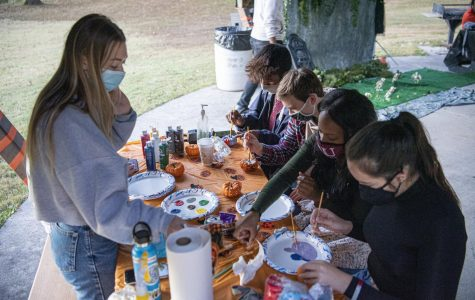Grace Durocher, a biochemistry major, helps out fellow students paint pumpkins at the Moon Light on the Lake event Saturday, Oct. 17, 2020, near campus lake.