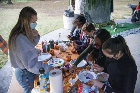 "Grace Durocher, a biochemistry major, helps out fellow students paint pumpkins at the Moon Light on the Lake event Saturday, Oct. 17, 2020, near campus lake. ""This was just a good way to get people out, because of Coronavirus, all these students have been stuck in their dorms with nothing to do. So we wanted to offer a safe setting for people to get out, below off some stress, meet some new friends, and just have a good night,"" Durocher said."