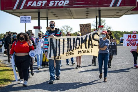 A group of protesters marches towards the Pulaski County Detention Center on Saturday, Oct. 3, 2020, in Ullin, IL. The facility is operated by ICE and has 78 confirmed cases of COVID-19. The protest was put on by the Southern Illinois Immigrant Rights Project and Midwest Council for Civil Rights. The goal was to demand health inspections for inmates.