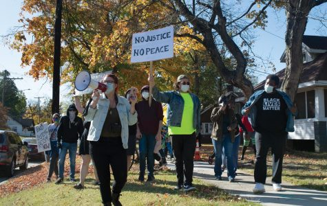 """Protestors march down a street in Carbondale, Ill. chanting """"Black Lives Matter"""" in a counter-protest to the passing Trump supporters Saturday, Oct. 17, 2020, in  Carbondale, Ill."""