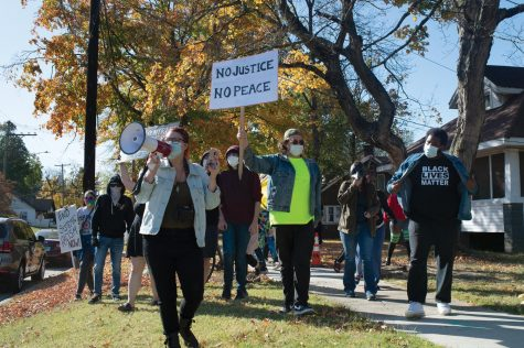"Protestors march down a street in Carbondale, Ill. chanting ""Black Lives Matter"" in a counter-protest to the passing Trump supporters Saturday, Oct. 17, 2020, in  Carbondale, Ill."