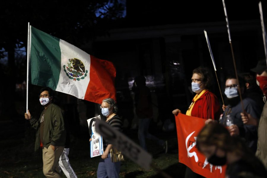 SIU Cinema and Advertising student, Tómas Cortez, carries a Mexican flag as he marches with members of local activist groups to protest against the status quo in American politics on the day after the election, Wednesday, November 4, 2020, in Carbondale, IL.  Cortez, 21, and the group of around 40 protesters marched from the town square pavilion to the US General Services Administration building and then back to the pavilion.