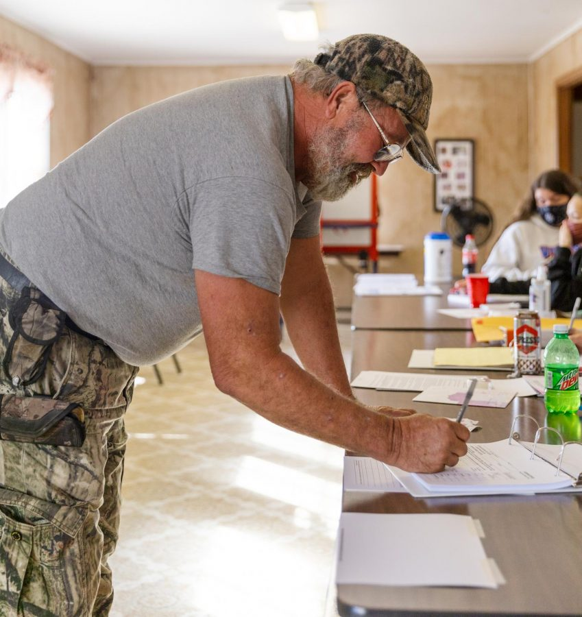 David Hester signs in to receive his ballot at the Senior Center in Belknap, Ill. Tuesday, Nov. 3, 2020.