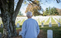 Kenny Johnson, a retired Air Force veteran, looks upon a grave at Mound City National Cemetery during Veterans Day on Wednesday, Nov. 11, 2020 in Mound City, Ill. Johnson has only been coming to the cemetery for the last couple of years, but says he finds it to be a peaceful place to go and walk down row by row, reading information from soldiers' tombstones.