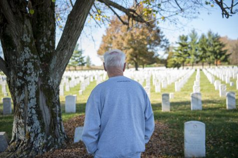 Kenny Johnson, a retired Air Force veteran, looks upon a grave at Mound City National Cemetery during Veterans Day on Wednesday, Nov. 11, 2020 in Mound City, Ill. Johnson has only been coming to the cemetery for the last couple of years, but says he finds it to be a peaceful place to go and walk down row by row, reading information from soldiers
