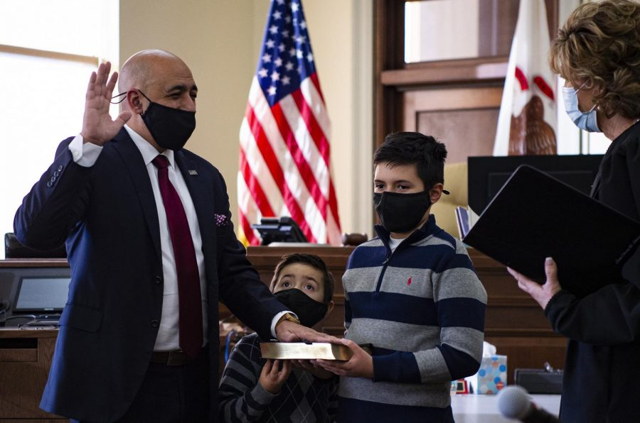 State's Attorney Joe Cervantez, is sworn in by presiding judge Christy Solverson, while Cervantez's sons Cason, 7, and Canon, 10, stand by during the ceremony at Jackson County Courthouse in Murphysboro, Ill. Dec. 1, 2020.