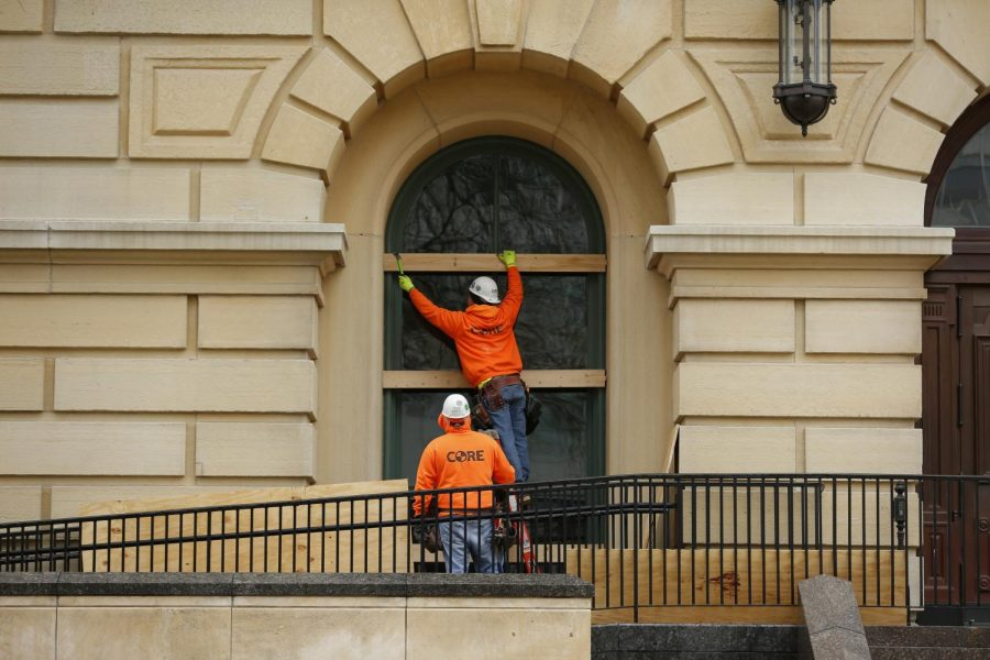 Workers board up windows at the Illinois State Capitol building on Saturday in Springfield in preparation for anticipated violence leading up to Biden's inauguration.  The FBI released a memo recently to law enforcement agencies across the country warning about potential violent protests at all 50 state capitols after the deadly mob attack on the U.S. Capitol last week.