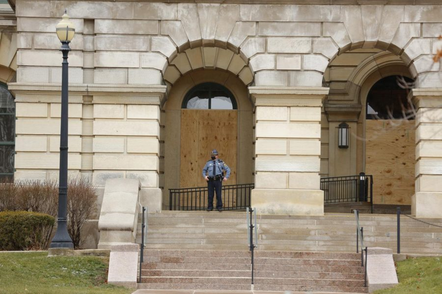 A State Capitol police officer stands watch in front of boarded up windows at the Illinois State Capitol building on Saturday in Springfield.  The FBI released a memo recently to law enforcement agencies across the country warning about potential violent protests at all 50 state capitols after the deadly mob attack on the U.S. Capitol last week.