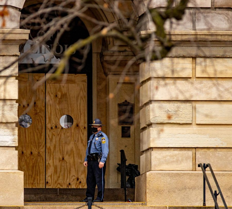 A state capitol police officer stands in front of the boarded up entrance to the Illinois State Capitol building on Saturday, Jan. 16, 2021 In Springfield, Ill.