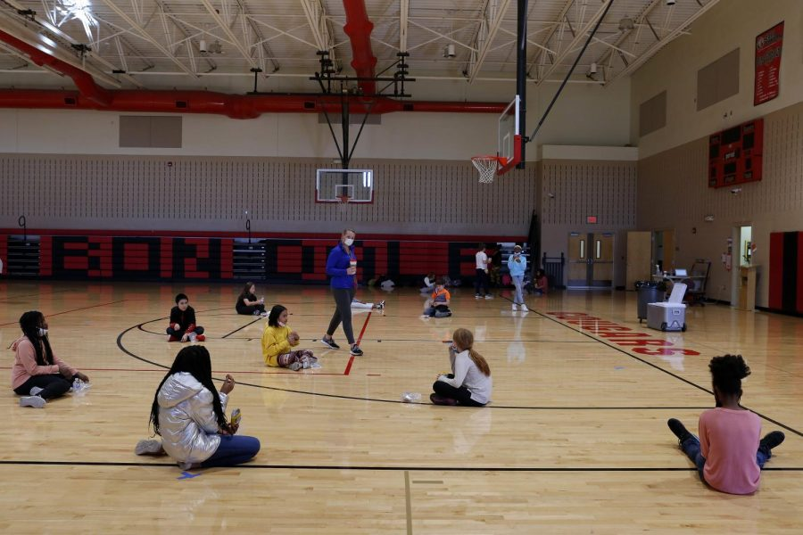 Carbondale Middle School physical education teacher, Coach Haley Karayiannas, center, chats with her socially distanced students on the last day of in-person learning, Friday, November 13, 2020.