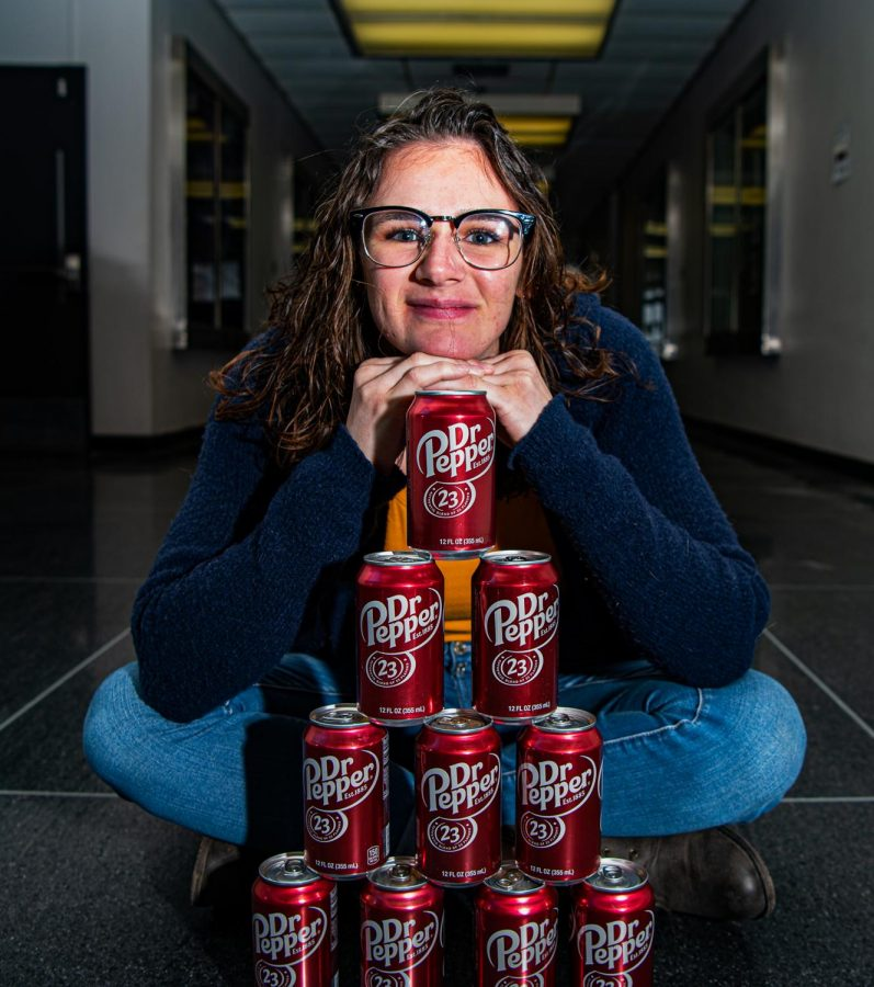 Marianne Haines poses with a stack of Dr. Pepper soda cans in the Communications building Wednesday, Jan. 27, 2021 at SIU. Haines, a junior at SIU studying biomedical science, was selected as a finalist in the Dr. Pepper tuition giveaway. Haines competed against another finalist to win a grand prize of $125,000 in tuition.