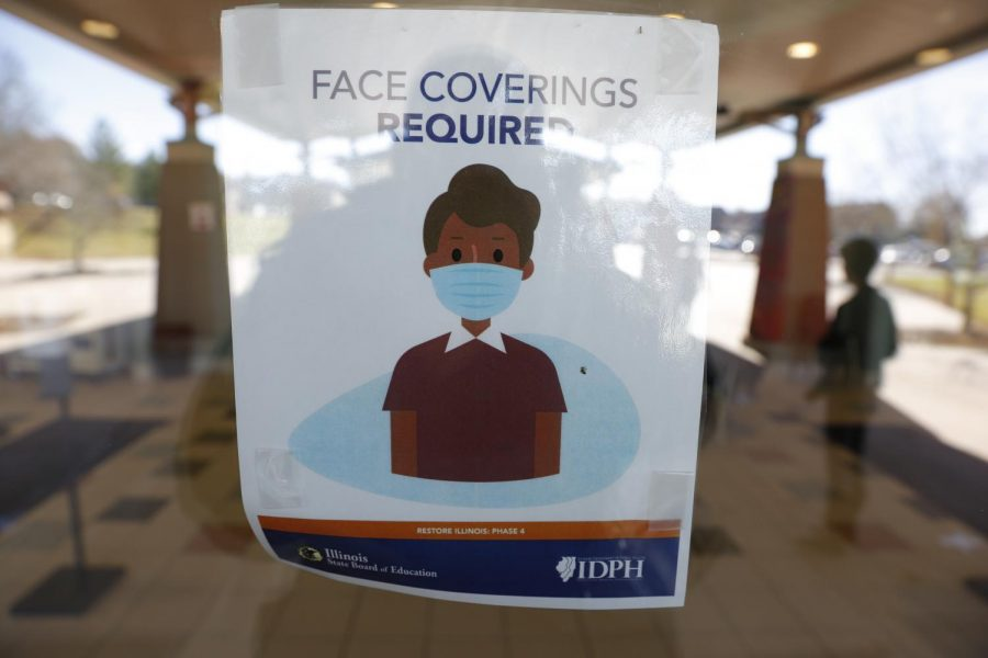 An Illinois State Board of Education sign on the front door of the Carbondale Middle School instructs anyone entering that face masks are required, Friday, November 13, 2020.  Angel Chevrestt // @sobrofotos