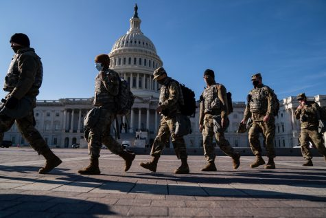 Members of the National Guard, outside the U.S. Capitol Building, a day after the House of Representatives impeached President Donald Trump, and over a week after a pro-Trump insurrectionist mob breached the security of the nation